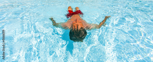 attractive man enjoys swimming in the pool