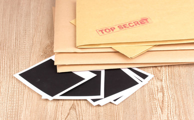 Envelopes with top secret stamp with photo papers close-up