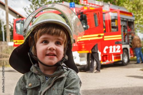 Leinwanddruck Bild Kleiner Junge mit Feuerwehrhelm