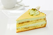 Slice of pistachio sponge cake with fondant icing and coffee