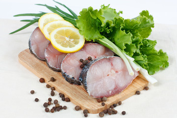 Fillet of fresh raw fish with herbs, lemon and spicy peppers