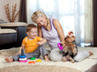mother, child boy and pet dog playing together indoor