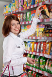 Pretty woman buyer in grocery shop at shelves with products poster