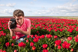 Yong man with old photo camera in field with tulips