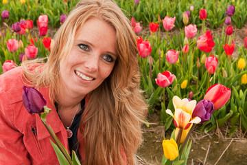 Dutch blond girl picking flowers in tulips field