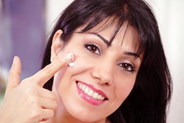 Smiling adult female applying face moisturizer