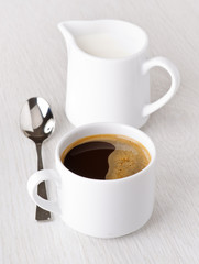 cup of coffee and milk jug, with spoon