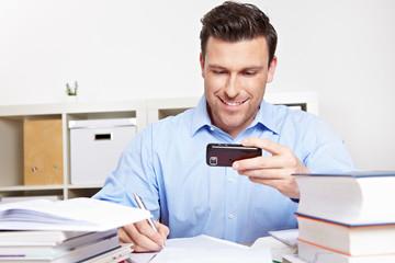 Mann schaut beim Lernen auf Smartphone
