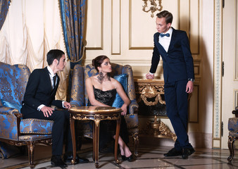 Two men and woman conversing in luxury interior