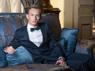 Young blond man with blue eyes in luxury interior