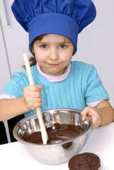 Niña cocinando crema de chocolate,torta