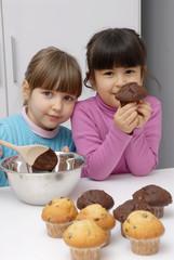 Niñas cocinando tortas de chocolate y vainilla.