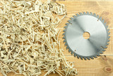 Circular saw blade on a wooden and sawdust background