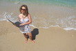 Curly hair young woman with her laptop at the beach