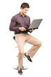 Young man sitiing on a stool and working on a laptop