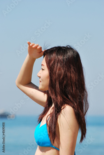 Asian girl in a bikini looking at the horizon3