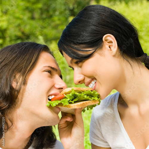 Young couple eating together outdoors