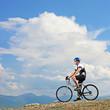 A man posing with a mountain bike on a ridge