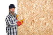 Carpenter points a sheet of plywood