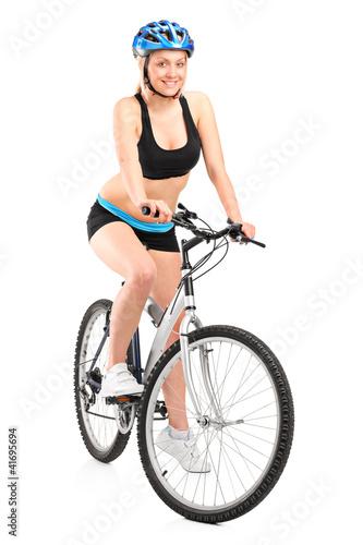 Portrait of a smiling female biker with helmet sitting on a bike