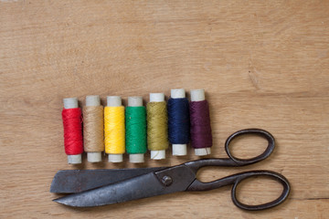 Old scissors and color threads on wood background