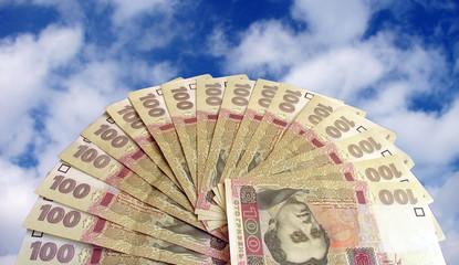 fan-shaped money over sky (hrivna)