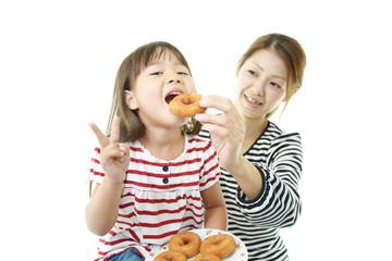 おいしそうにドーナツを食べるVサインの女の子