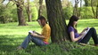 Two students sitting in the park and learning, tracking shot
