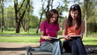 Two student girls learning outdoors, tracking shot
