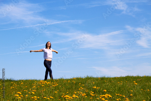 smiling young girl dancing on green grass