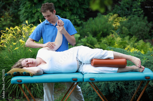 Physical therapist massaging pregnant woman
