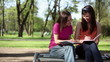 Two female students sitting in the park and making notes