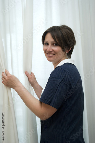 Maid drawing curtain