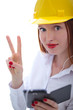 Young beautiful female with yellow helmet showing the v sign