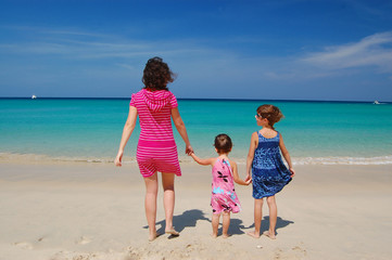 Family beach vacation. Happy mother with kids near sea