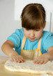 Pequeña niña cocinando y preparando masa en una cocina.