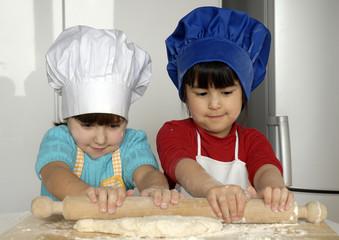 Dos niñas cocinando masa y pizza en una cocina.
