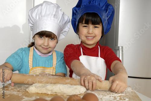 Dos ni as cocinando masa y pizza en una cocina de - Nina cocinando ...