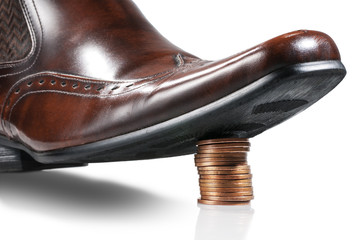 Shiny businessman shoe step on the stack of coins. Isolated.
