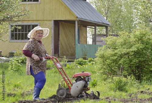 Женщина на даче с мотоблоком.
