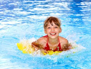 Child swimming on inflatable beach mattress.