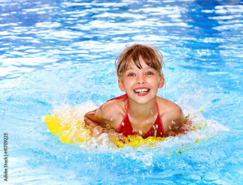 Child swimming on inflatable beach mattress.