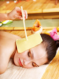 Fototapety Woman getting massage with ear candle .