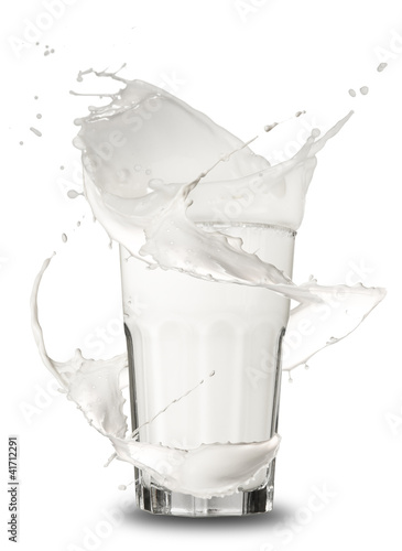 Milk splashing out of glass, isolated on white background