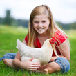 girl sitting on a meadow with her chicken