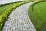 Fototapety The Stone block walk path in the park with green grass backgroun