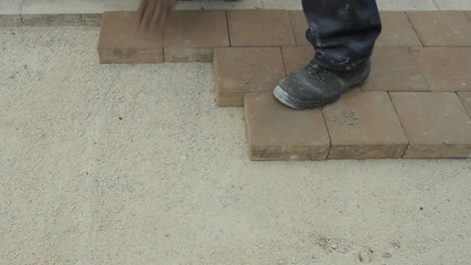Worker laying brick tiles on the road
