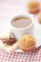 bar of chocolate,tea and muffin on plaid fabric