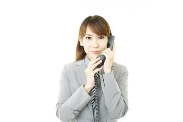 電話対応をする笑顔のオフィスレディー