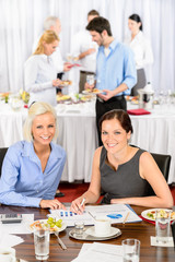 Two business women work during catering buffet